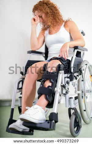 Dejected woman with her knee in a brace and a post-operative scar sitting in a wheelchair with her head resting on her hand in a disability and health care concept