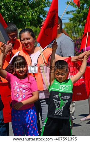 DELANO, CA - APRIL 17, 2016: Two young children are enjoying their participation in today's march by the members of the United Farm Workers for agricultural workers' rights. - stock photo