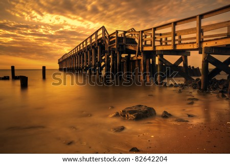 Delaware Bay Fishing Pier illuminated by golden morning light. - stock photo