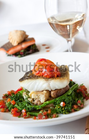 Delectable Atlantic Cod served with fingerling scallion hash, braised rapini, saffron red peppers and bagna cauda sauce. Paired perfectly with white wine. - stock photo