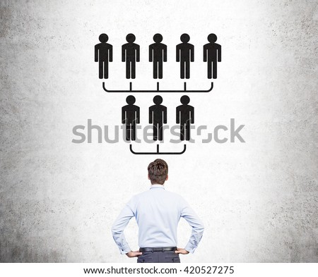 Delegate concept with businessman looking at hierarchy sketch on concrete wall - stock photo