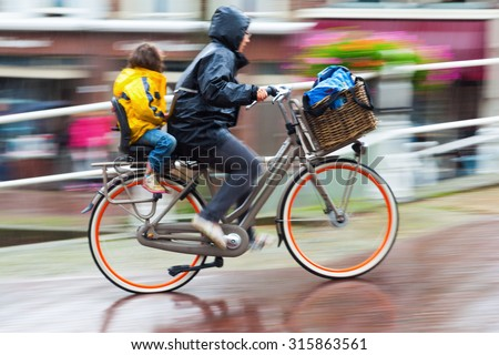 DELFT, NETHERLANDS - SEPTEMBER 04, 2015: unidentified cyclist on a rainy day. In NL almost as many kilometres are covered by bicycle as by train. It is estimated that they have at least 18 mio bicycle - stock photo