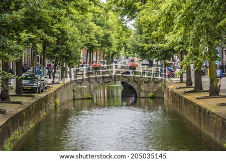 DELFT, THE NETHERLANDS - JUNE 17, 2014: City view with unknown people from the center of Delft with a canal and town houses. Delft is known for a large number of channels in historical city center.