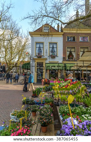 Delft, the Netherlands, March 5, 2016: Delft market square with typical Dutch architecture and flowers for sale