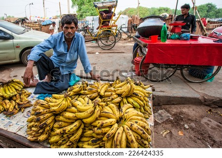 DELHI - APR 16: Market vendor selling bananas on a local market on April 16, 2011 in Delhi, India. India ranks second worldwide in farm output. Agriculture employs 52.1% of the total workforce. - stock photo