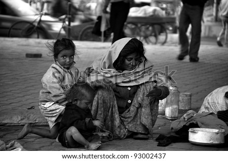 DELHI - DECEMBER 21: A mother feeds her children what little they have to eat (in the road) on December 21, 2009 in Delhi, India. More than 37% of the people in India live below the poverty line. - stock photo