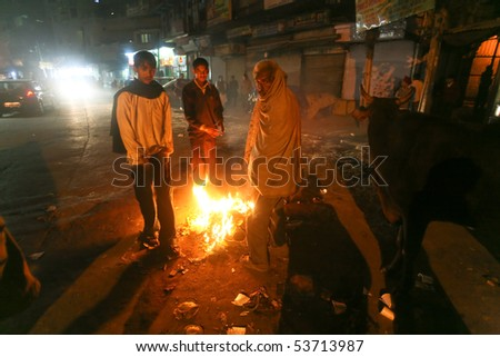 DELHI - FEB 14: Men standing around street fire at night on February 14, 2008 in Delhi, India. Winters can get quite cold in the desert capital.