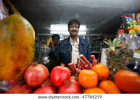 DELHI - FEBRUARY 26: Juice stall owner preparing fresh fruit juices on February 26, 2008 in Dehli, India. Fresh juices are great alternatives to polluted drinking water in India. - stock photo