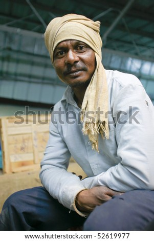 DELHI - FEBRUARY 19: Portrait of male worker with headscarf at train station on February 19, 2008 in Delhi, India. These men are not paid more than 2,5 dollars a day. - stock photo