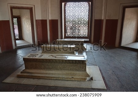 Delhi, India - Apr 27 2014: Inside the Humayun's Tomb, 3 stone tombs are located in one room, sunshine is coming through the beautiful windows in islamic style.