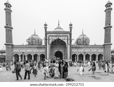 Delhi, India - August 2 2014:  Muslim men and tourists gather in front of the famous Jama Mosque in Old Delhi in India capital city. - stock photo