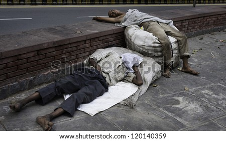 DELHI, INDIA - AUGUST 07: Two unidentified homeless men with their sparse belongings asleep on the side of a busy road on August 07, 2011 in central Delhi, India. - stock photo