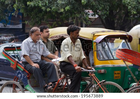 DELHI, INDIA-AUGUST 29, 2011: Unidentified Indian trishaw driver  in Delhi, India. Bicycle rickshaw on the street of Delhi. - stock photo