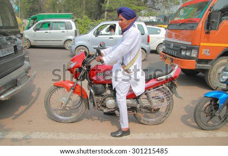 DELHI, INDIA - FEBRUARY 18, 2015: a man in traditional clothes on motorcycle stops in traffic jam in Delhi, India - stock photo