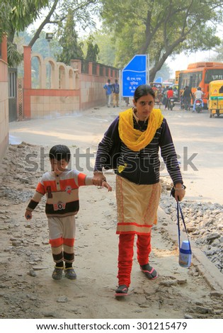 DELHI, INDIA - FEBRUARY 18, 2015: mom leads her son to home in poor district of Delhi, India - stock photo