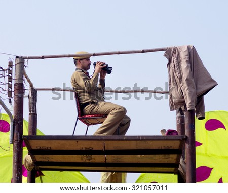 Delhi, India - Fedruary 12, 2014: Unidentified Policman on watchtower looking in field glass at annual Surajkund fair at the outskirts of Delhi. - stock photo