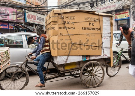 DELHI , INDIA - JANUARY 24: A bicycle rickshaw porter with large load in crowded streets on January, 24 2015 in Old Delhi, India. - stock photo