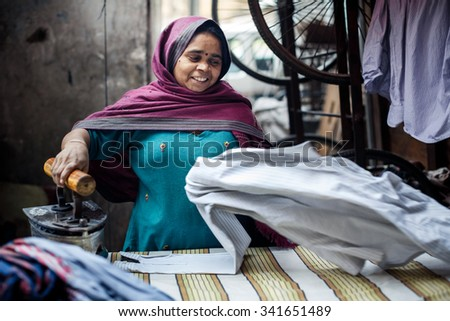 DELHI, INDIA - JANUARY 4, 2015: Mature Indian woman ironing clothes on January 4, 2015 in Delhi, India - stock photo