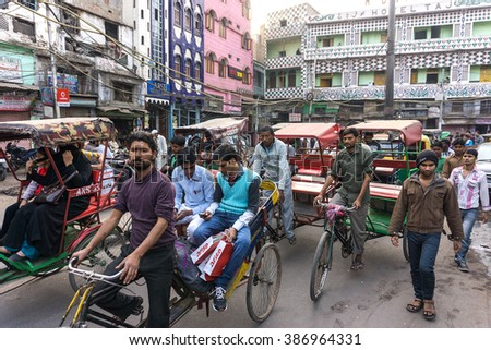 DELHI, INDIA - March 02: Morning on a street at March 02, 2016 in Old Delhi, India. Indian capital still uses man powered rickshaws as a usual mean of transport. - stock photo