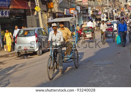 DELHI, INDIA - NOV 8: Rickshaw rider transports passenger early morning on November 08,2011 in Delhi, India. Cycle rickshaws were introduced in Delhi in the 1940's and have a fixed quota of licenses. - stock photo
