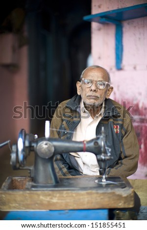 DELHI, INDIA - NOV 18: Unidentified old man is sewing in a classical street in Old Delhi. November 18, 2012 in Delhi, India. The lifestyle in old delhi is still well kept like that in 100 years ago. - stock photo