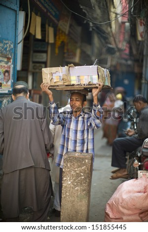 DELHI, INDIA - NOV 18: Unidentified people works in a classical street in Old Delhi. November 18, 2012 in Delhi, India. The lifestyle in old delhi is still well kept like that in 100 years ago. - stock photo