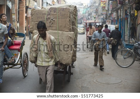 DELHI, INDIA - NOV 18: Unidentified workers move stuffs in a classical street in Old Delhi. November 18, 2012 in Delhi, India. The lifestyle in old delhi is still well kept like that in 100 years ago. - stock photo