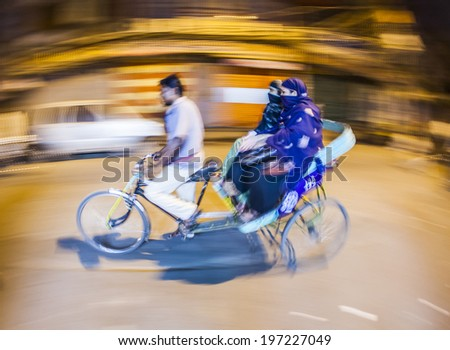 DELHI, INDIA - NOVEMBER 10, 2011: Street traffic in Delhi. Senior man transport in old tricycle rickshaw a Lady in Delhi, India. Old buildings and cars in background. Panning, motion blur.