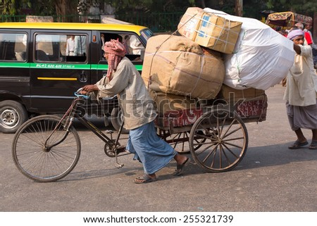 DELHI, INDIA - NOVEMBER 5: Unidentified cycle rickshaw walks with goods on November 5, 2014 in Delhi, India. Cycle rickshaw is popular mode of travel for short distance transits in the city.