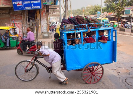 DELHI, INDIA - NOVEMBER 5: Unidentified kids take cycle rickshaw to school on November 5, 2014 in Delhi, India. Cycle rickshaws are a popular mode of travel for short distance transits in the city. - stock photo