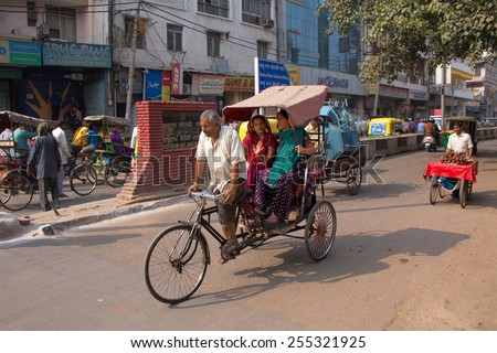 DELHI, INDIA - NOVEMBER 5: Unidentified people ride cycle rickshaw on November 5, 2014 in Delhi, India. Cycle rickshaw is popular mode of travel for short distance transits in the city. - stock photo