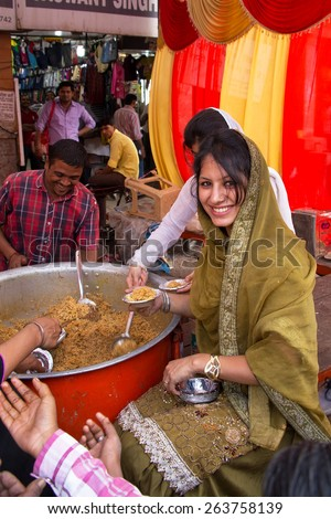 DELHI, INDIA - NOVEMBER 5: Unidentified woman gives away rice during Guru Nanak Gurpurab celebration on November 5, 2014 in Delhi, India. This festival celebrates the birth of the first Sikh Guru. - stock photo
