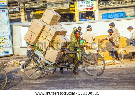 DELHI, INDIA - OCT 16: Rickshaw rider transports heavy goods early morning on October 16,2012 in Delhi, India.Cycle rickshaws were introduced in Delhi in the 1940's and have a fixed quota of licenses. - stock photo