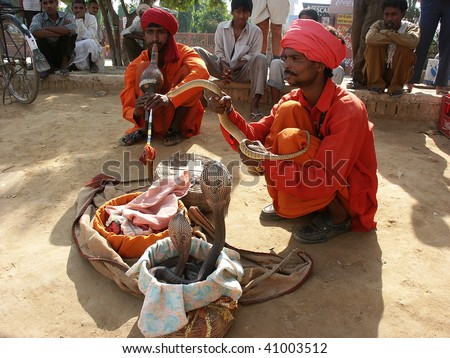 DELHI, INDIA - OCTOBER 25: Two snake charmers performing in the street on October 25, 2002 in Delhi, India. - stock photo