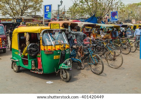 DELHI, INDIA - 19TH MARCH 2016: Tuk Tuk Rickshaws parked on a street in central Delhi during the day. People can be seen. - stock photo