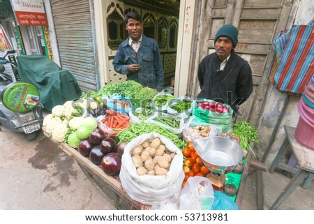 DELHI - JAN 15: Two male stallholders selling vegetables on street on January 15, 2008 in Delhi, India. Supermarkets are rare and people mostly shop at street markets. - stock photo