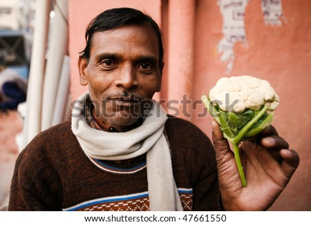 DELHI - JANUARY 31: Vegetable street vendor displaying his produce on January 31, 2008 in Delhi, India. Most mobile vendors are illegal and have to either run away from the police or pay them bribes. - stock photo