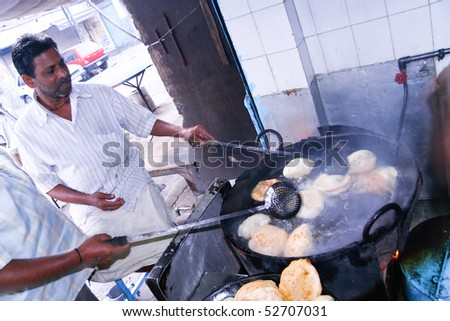 DELHI - OCTOBER 28: Two men preparing Puri in small roadside restaurant on October 28, 2007 in Delhi, India. Chapatis are the staple diet of all Indians. - stock photo
