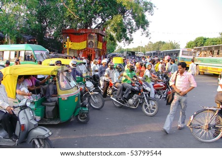 DELHI - SEP 22: Traffic jam with rickshaws, motorbikes, and vans on busy city street on September 22, 2007 in Delhi, India. All public transport runs on CNG to help cut pollution levels. - stock photo