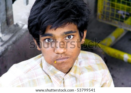 DELHI - SEP 22: Young street kid eating on ground on September 22, 2007 in Delhi, India. UNHCHR has estimated that India has the largest population of street children in the world. - stock photo