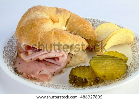 "Deli Coldcuts on Croissant with ""Bread and Butter"" pickles and potato chips."