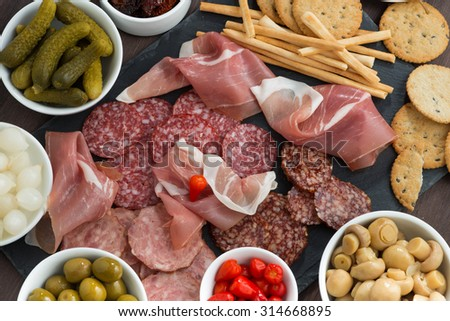deli meat snacks, sausages and pickles on a blackboard, top view, horizontal - stock photo