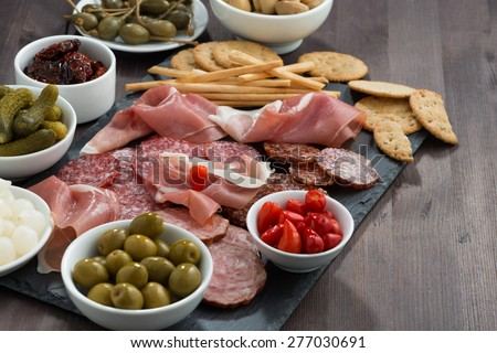 deli meat snacks, sausages and pickles on a dark wooden table, horizontal - stock photo