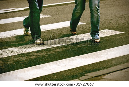 Deliberate high contrast picture of two pedestrians crossing crosswalk - stock photo