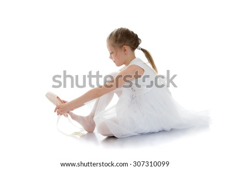 Delicate adorable little ballerina in a beautiful white translucent dress sitting on the floor, clothes and shoes for dancing-Isolated on white background - stock photo
