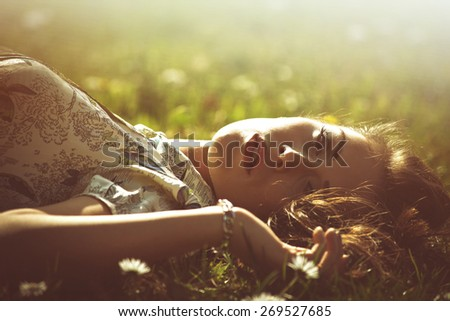 delicate beautiful young woman enjoy in sun lie in grass retro look and colors - stock photo