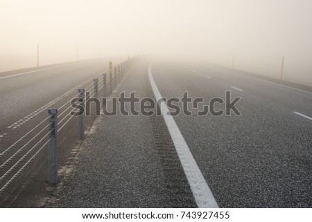 Delicate beige background for pasting text. Road in Iceland. Beautiful fog and sunlight