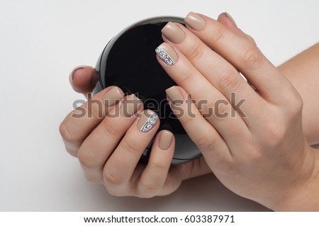Delicate beige manicure on short square nails with silver and monograms with a black ball in hands