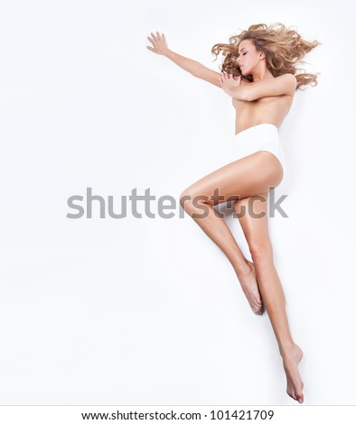 Delicate blond woman lying on a white background - stock photo
