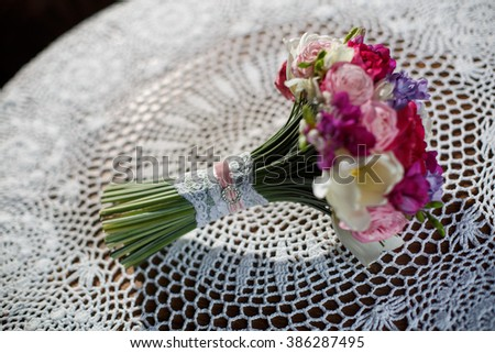 delicate bouquet bride in a white knitted tablecloth wedding floristry and decor wedding brides the wedding bouquet gorgeous floral arrangement bridal bouquet of roses, violets, tulips - stock photo